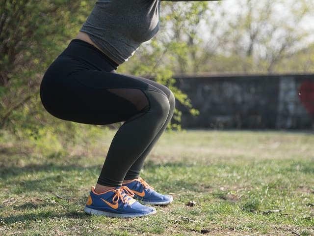 Jeune femme exécutant un squat avec haltères
